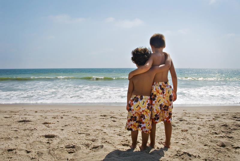 two brothers looking at ocean